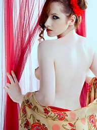 Redhead beauty stripping in white studio with red..